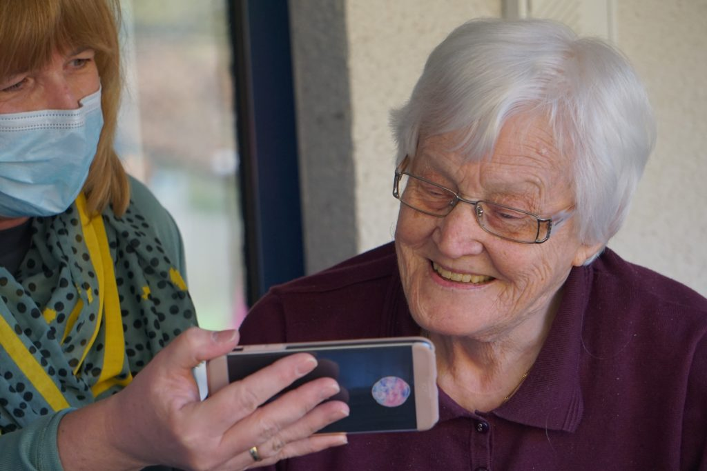 woman showing image on phone to elderly lady